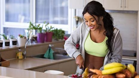 happy woman cutting fruit