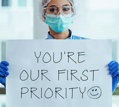 """Woman holding sign saying """"You're our first priority""""."""